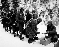 Chow is served to American Infantrymen on their way to La Roche, Belgium.  347th Inf. Regt. January 13, 1945.  Newhouse.  (Army)  <br /> FILE #:  111-SC-198849<br /> WAR & CONFLICT BOOK #:  1075