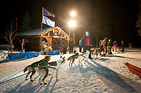 Ed Iten checks into the Rohn checkpoint while  volunteer checkers help hold her team and walk them to a parking spot during Iditarod 2009