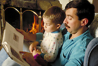 Father reading boy a book while at home in front of fireplace. Family. Douglaston NY.