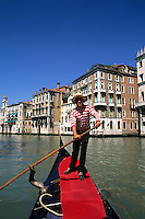 Romantic gondola with gondolier in traditional striped shirt in picturesque Venice Ital