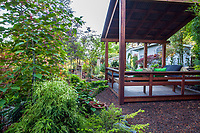Backyard covered deck outdoor room with built in benches in California plant collector garden - Carol Brant