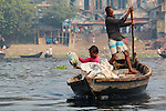 A boatman on the Buriganga River, Dhaka, uses all his strength to paddle a customer and his goods across the river