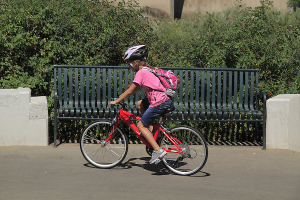 Young girl riding her bike on a sidewalk in Denver, Colorado. .  John offers private photo tours in Denver, Boulder and throughout Colorado. Year-round.