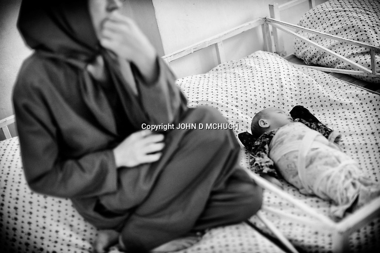A recovering drug addict and her 4 month old baby, also addicted to opium, are seen in a drug treatment clinic in Mazar-e Sharif, 26 September 2013. The woman had suffered heavy bleeding after giving birth and her mother in law insisted she take heroin to manage the pain and treat the problem. As her baby was crying a lot, the mother was told to give it opium too. (John D McHugh)