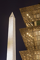 The angular metal architecture of the Smithsonian National Museum of African American History and Culture contrasts with the stone structure of the Washington Monument at night in Washington, DC.