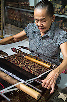 Bali, Indonesia.  Woman Weaving Using Back-strap Loom to Weave  Geringsing Cloth, a Specialty of Tenganan Village.