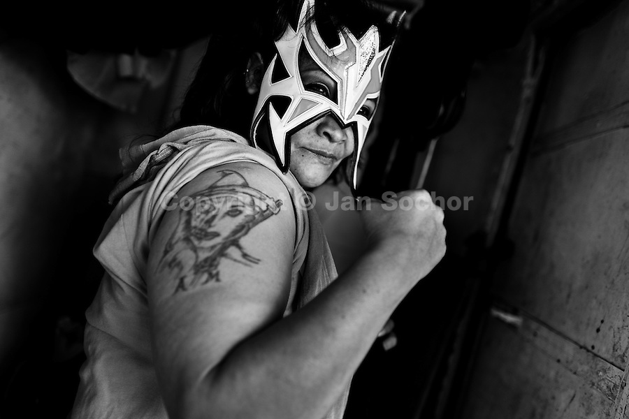 """A female Lucha libre wrestler La Fugitiva poses for a picture in the backstage before a fight at a local arena in Mexico City, Mexico, 30 April 2011. Lucha libre, literally """"free fight"""" in Spanish, is a unique Mexican sporting event and cultural phenomenon. Based on aerial acrobatics, rapid holds and the use of mysterious masks, Lucha libre features the wrestlers as fictional characters (Good vs. Evil). Women wrestlers, known as luchadoras, often wear bright shiny leotards, black pantyhose or other provocative costumes. Given the popularity of Lucha libre in Mexico, many wrestlers have reached the cult status, showing up in movies or TV shows. However, almost all female fighters are amateur part-time wrestlers or housewives. Passing through the dirty remote areas in the peripheries, listening to the obscene screams from the mainly male audience, these no-name luchadoras fight straight on the street and charge about 10 US dollars for a show. Still, most of the young luchadoras train hard and wrestle virtually anywhere dreaming to escape from the poverty and to become a star worshipped by the modern Mexican society."""