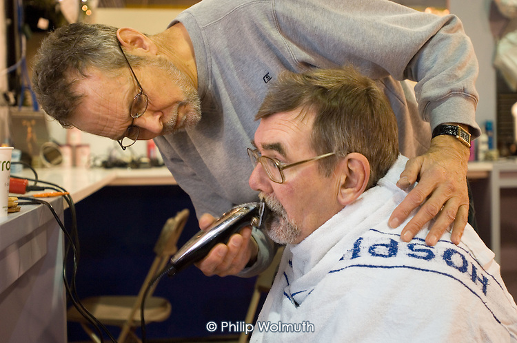 A homeless 'guest' gets a haircut and beard trim from a volunteer barber at the Crisis Open Christmas shelter in the London Arena, Docklands.