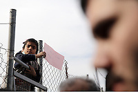 "Pictured: A young boy with a ""Don't Like Camp"" placard on top of the fence of the camp Monday 06 February 2017<br /> Re: Scuffles between migrants and police broke out during a visit by Immigration Policy Minister Yiannis Mouzalas at the Elliniko migrant camp located in the former airport in the outskirts of Athens, Greece."