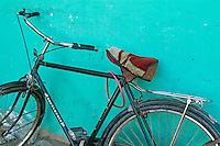 Old black bike parked against a green wall, Al-Qusair, Egypt.