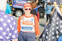 "A woman wears Trump 2020 campaign buttons, shirt, and hat reading ""Keep America Great"" as alt-right organization Super Happy Fun America demonstrates against facemasks, vaccines, and pandemic closures, and in support of the reelection of President Donald J. Trump near the residence of Massachusetts governor Charlie Baker in Swampscott, Massachusetts, on Sat., Sept. 26, 2020. Super Happy Fun America is most well known for organizing the Straight Pride Parade in Boston on August 31, 2019."