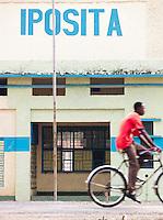A man cycling past the Post Office in Gisenyi, Rwanda
