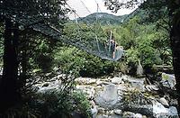 A tramper on a swingbridge accross the Little Wanganui River on the Wangapeka Track - Kahurangi National Park