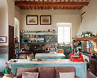 The rustic farmhouse kitchen features a massive old sink in local sandstone with a splash back of Neapolitan hand-painted tiles