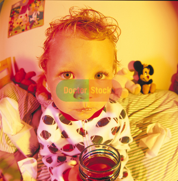 portrait of sick young child drinking juice in bed