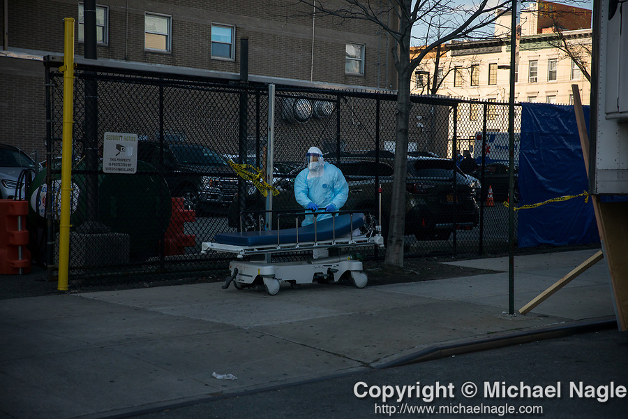 A healthcare worker wheel a hospital bed after transporting a deceased person to a refrigerated trailer serving as a temporary morgue outside of Wyckoff Heights Medical Center during the coronavirus pandemic in the Brooklyn borough of New York, the United States, Monday, April 6, 2020.  More than 10,000 people have died from COVID-19 in the U.S..  (Xinhua/Michael Nagle)