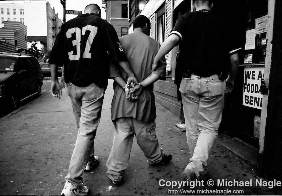 BRONX  --  SEPTEMBER 23, 2003:  The NYPD Firearms Investigation Unit detectives handcuff a man for questioning after serving a search warrant and arresting men selling cocaine and heroin from a bodega on September 25, 2003 in the Bronx.  The men working at the bodega offered to sell guns to an undercover detective, while selling cocaine and heroin.  (PHOTOGRAPH BY MICHAEL NAGLE)