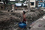 A child bathing by the side of a street at Joana Village in Jajmau. Waste water pollution is a big problem in Jajmau area. Waste water from the tanneries are used for irrigation which contaminates the ground water and fresh water flowing through faulty underground pipe lines. Kanpur, Uttar Pradesh, India. Arindam Mukherjee
