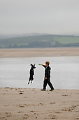 A boy plays with a dog on the beach at Borth-y-Gest, Porthmadog, North Wales