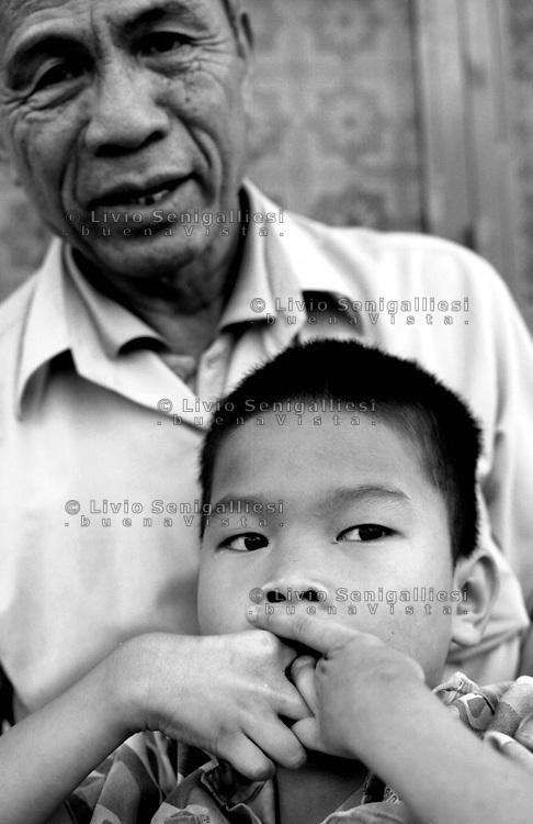 Sa-Thay / Kontum / Vietnam.<br /> Due generazioni vittime dell'agente arancio.I reduci e i loro figli o nipoti portano nel DNA le conseguenze della diossina nebulizzata dagli aerei USA tra il 1961 e il 1971 sulle foreste nel delta del Mekong e lungo il confine col Laos col fine di scovare e colpire i Vietcong.In primo piano il piccolo Nguyen Van Nam di 14 anni. Non cammina, non sente.Vive dalla nascita su una stuoia contorcendosi giorno e notte senza tregua.<br /> Foto Livio Senigalliesi.<br /> Sa-Thay / Kontum / Vietnam.<br /> Two generations victims of Agent Orange (defoliant).The veterans and their sons are still suffering becouse of dioxine sprayed on the forest by US airplanes between 1961 and 1971 along the Vietnam and Laos border and Mekonk delta.In the picture Nguyen Van Nam (14) living in Sa-Thay a little village near Kontum, one of the place more affected by Agent Orange sindrome.<br /> Photo Livio Senigalliesi
