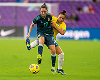 ORLANDO, FL - FEBRUARY 18: Mariana Larroquette #19 of Argentina is defended by Andressa #7 of Brazil dribbles during a game between Argentina and Brazil at Exploria Stadium on February 18, 2021 in Orlando, Florida.