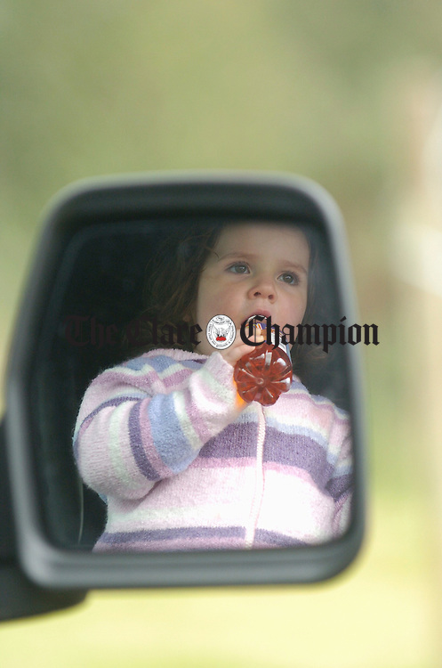Young Emma Devine watches all the actuivity for the comfort of a parked van at the official opening of the Inch School and Community field. Photograph by John Kelly.