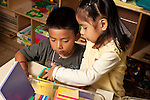 Education preschool 3-4 year olds boy and girl building together with magetic blocks