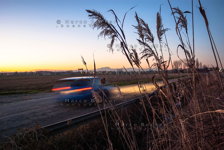 Parco agricolo Sud Milano presso Locate di Triulzi. La scia di luce dei fari di un'automobile che percorre veloce una strada tra i campi al tramonto ---  Rural Park South Milan near Locate di Triulzi. The trail of lights of a car going fast along a road between fields at sunset