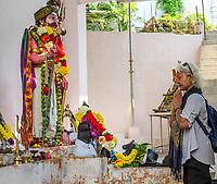 Worshiper Praying in front of Hindu Deity, Hindu Sri Maha Muneswarar Temple, Kuala Lumpur, Malaysia.