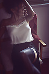 Beautiful sexy woman sitting in a chair half dressed in a night shirt and stockings in a dimly lit room Image © MaximImages, License at https://www.maximimages.com
