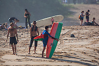 Friends commiserate with a fellow surfer holding a broken surfboard, Waimea Bay, North Shore, O'ahu.