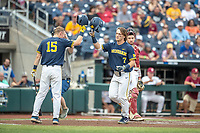 Michigan Wolverines outfielder Jesse Franklin (7) is greeted by teammate Jimmy Kerr (15) after his first inning home run in Game 6 of the NCAA College World Series against the Florida State Seminoles on June 17, 2019 at TD Ameritrade Park in Omaha, Nebraska. Michigan defeated Florida State 2-0. (Andrew Woolley/Four Seam Images)