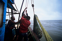 Artisanal fishing, commercial fishing, overfishing, Fisherman bring up net full of shrimp and bycatch onboard semi-industrial shrimp dragger. Maputo, Mozambique, Africa, Indian Ocean