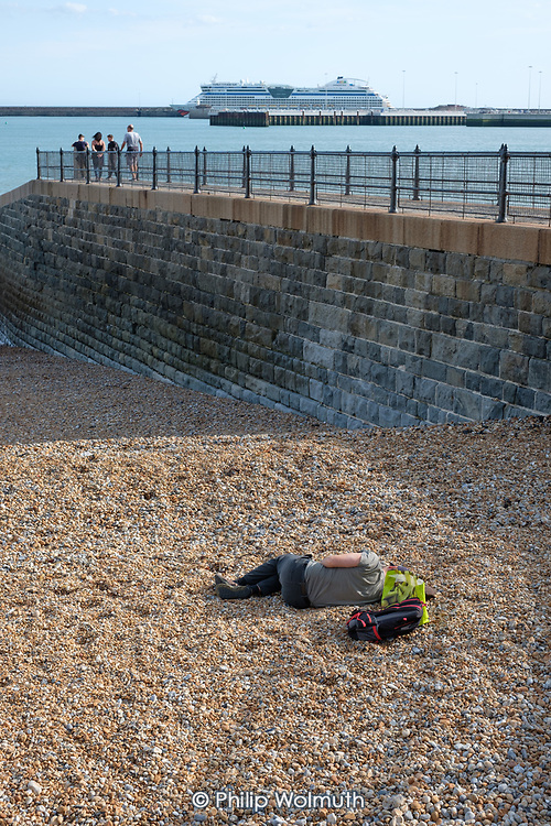 Young man sleeping on a pebble beach, and luxury cruise liner berthed at the Western Harbour, Dover, Kent.