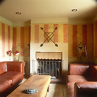 Albion House near Bath, the home of decorative painter Adam Calkin. A sitting room with a yellow and red striped finish on the walls. Two leather sofas face each other over a wooden coffee table.