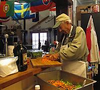 Pilot and chef Genero helps prepare dinner for a meeting of the Petaluma Area Pilots Association, Petaluma Municipal Airport, Petaluma, Sonoma County, California