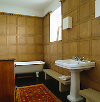 This bathroom at Bowling Green is lined with pale oak wood panelling and has a dark stained wooden floor