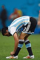 Ezequiel Garay of Argentina ties his shoe laces