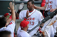 Designated hitter Rafael Devers (13) of the Greenville Drive is congratulated after scoring a run in a game against the Charleston RiverDogs on Sunday, May 24, 2015, at Fluor Field at the West End in Greenville, South Carolina. Devers is the No. 6 prospect of the Boston Red Sox, according to Baseball America. Charleston won 3-2. (Tom Priddy/Four Seam Images)