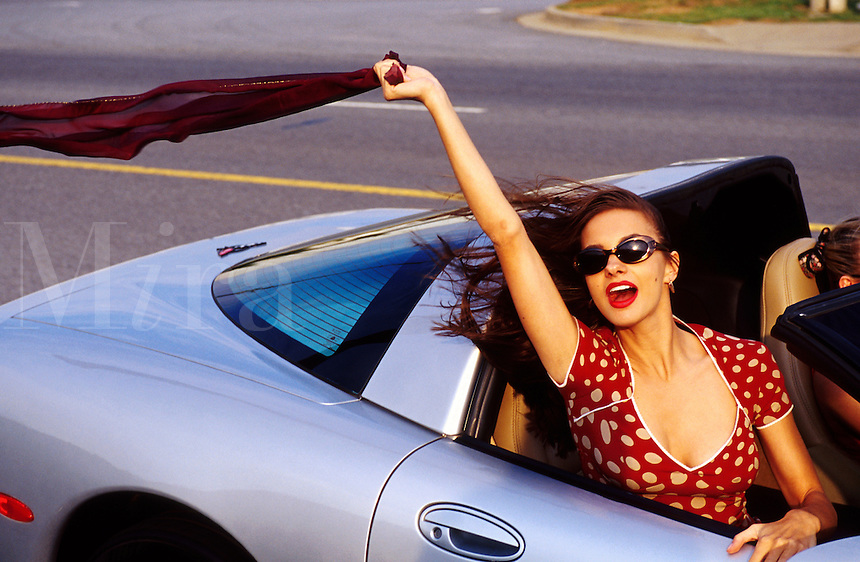 A smiling young woman lets her scarf blow in the wind as she rides in a silver Corvette convertible .