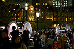 Tokyo, Japan - Pedestrians take pictures of the light wheels at the opening ceremony of the Tokyo Michiterasu 2013, in front of Tokyo Station on December 24, 2013. The illumination of this year presents the light wheels on light railway and the light train windows. The event starts from December 24th to 29th at around Tokyo Station. (Photo by Rodrigo Reyes Marin/AFLO)