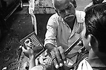 A street barber at his work on a street in Kolkata, India.