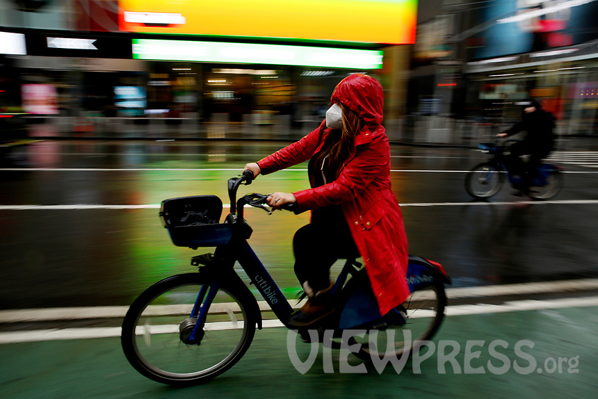 NEW YORK - NEW YORK - MARCH 24: A woman rides a bike at Times Square on March 24, 2021 in New York. With more people every day getting vaccinated transmission rates are dropping, arts an entertainment values should open at 33% capacity on April 2, as outdoor amusement parks will open at 25% capacity one week later (Photo by John Smith/VIEWpress)