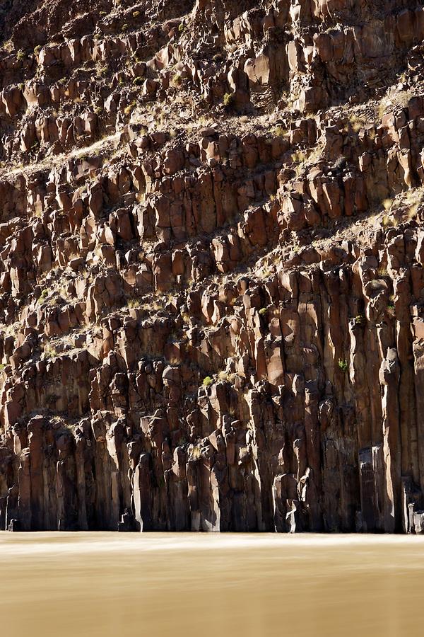 John Day River flowing under columnar basalt rock cliffs, central Oregon desert, USA
