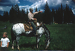 MAN ON HORSE WITH CHILD IN MEADOW