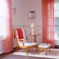 An antique chair and stool sit beside tall windows covered with pink lace curtains in this feminine space.