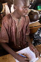 Senegal, Touba.  Boy  at Al-Azhar Madrasa, a School for Islamic Studies, writing in Arabic in his notebook.