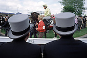 Racegoers watch the horses parade in the Paddock at Epsom Downs racecourse on Derby Day.