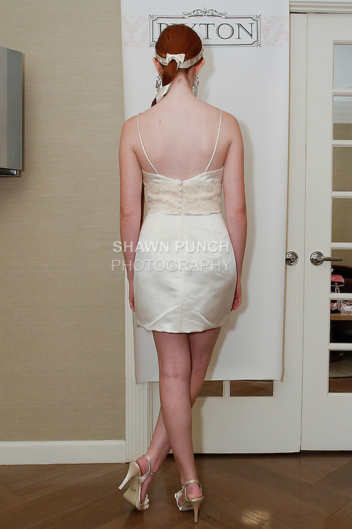 Model poses in a Lucy wedding gown from the Pixton Couture Bridal Spring 2014 collection, by Kimberly Pixton Millar, during New York Bridal Market Week Spring 2014.