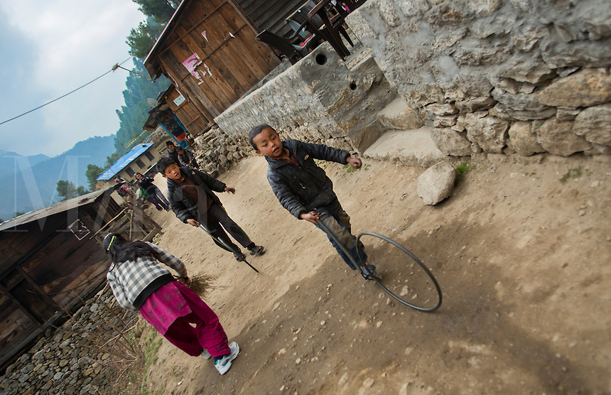 Nepal. Children playing in the streets with wheel of the village of Chhumowa, Solukhumbu remote Mt Everest    63